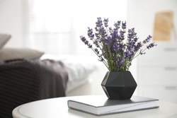 Beautiful lavender flowers and book on white table indoors. Space for text