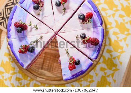 Beautiful layered berry cake with a purple, white and pink layer, decorated with raspberries and blueberries on top.  Cake in a cut on a wooden round board  in the restaurant. Close up. Top view. #1307862049