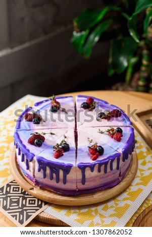 Beautiful layered berry cake with a purple, white and pink layer, decorated with raspberries and blueberries on top. Cake on a wooden round board on a wooden table in the restaurant. Close up #1307862052