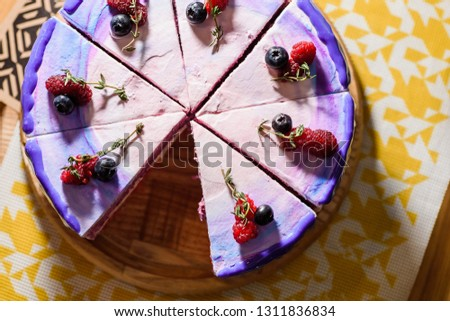 Beautiful layered berry cake with a purple, white and pink layer, decorated with raspberries and blueberries on top.  Cake in a cut on a wooden round board  in the restaurant. Close up. Top view. #1311836834
