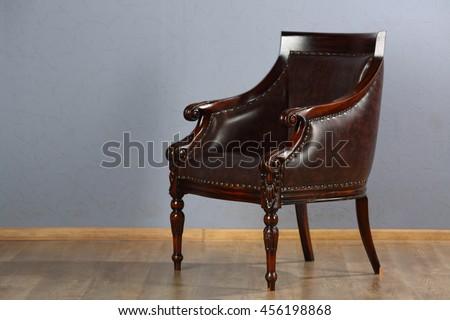 Beautiful leather armchair in retro style in studio is on wooden floor