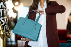 Beautiful leather purse in the girl's hand. Luxury bag on the background of black trousers in the interior. Fashionable modern accessory. horizontal photo