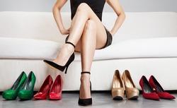 Beautiful leg woman sitting on the sofa with many high heels.Leg care . Love heels.