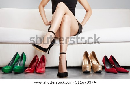 Beautiful leg woman sitting on the sofa with many high heels.Leg care . Love heels.
