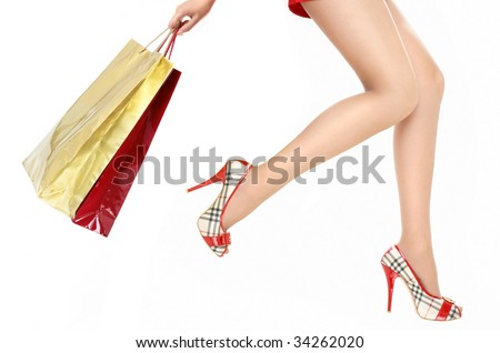 Beautiful legs of the running woman holding in a hand packages with purchases