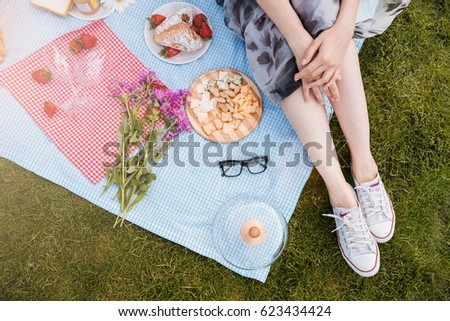 Beautiful legs of young woman in white sneakers sitting on blanket on green grass and having picnic
