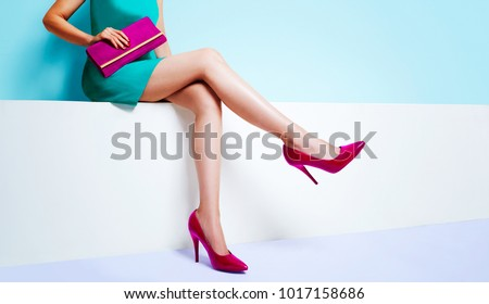 Beautiful legs woman sitting on the bench. With red pink purse and high heel shoes.  - Shutterstock ID 1017158686