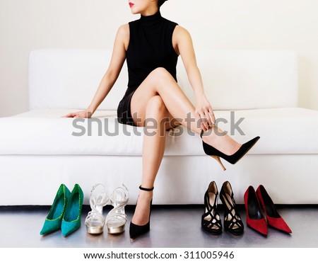 Beautiful legs. Woman trying many shoes. choosing.