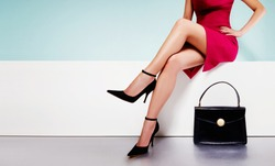 Beautiful legs woman wearing red dress with black purse hand bag with high heels shoes sitting on the white bench.  with copyspace.