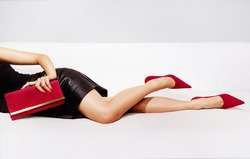 Beautiful legs woman with party bag and sexy dress laying on the couch. Red bag and red heels.