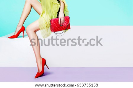 Beautiful legs woman with red heels shoes and purse handbag sitting on the white bench #633735158
