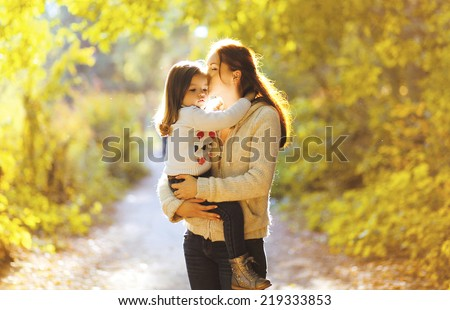 Beautiful lifestyle autumn photo mother and child walks evening in the park, warm sunlight