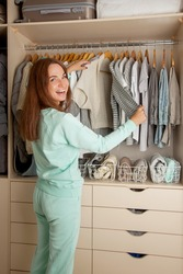 Beautiful light wardrobe with women's clothing. The girl hangs up and puts things in order in the closet.