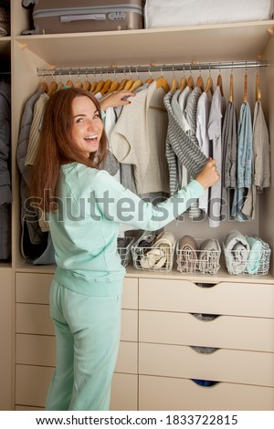 Beautiful light wardrobe with women's clothing. The girl hangs up and puts things in order in the closet. Foto stock ©