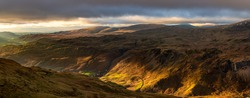 Beautiful light with panoramic view of Western Lake District fells and dramatic dark clouds in the sky.