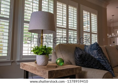 Beautiful light wooden side table with bright green leaves, oil lamp, and lamp on it. A neutral colored sofa is next to it, with shuttered windows behind it. Beautiful interior design. Stock photo ©