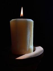 Beautiful light yellow beeswax pillar candle glowing in afternoon sun