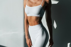 Beautiful lighting. Young caucasian woman with slim body shape is indoors at daytime.