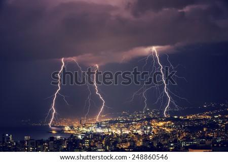 Beautiful lightning at night over gorgeous glowing Lebanon, majestic nighttime cityscape, stormy weather