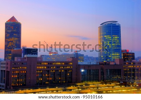 Beautiful lights of a sunset over a modern area of an old city with train TGV station in the foreground, Lyon, France.