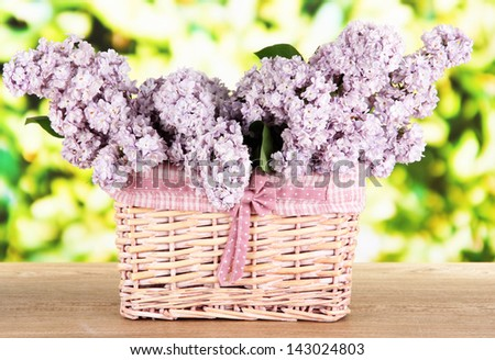 Beautiful lilac flowers on table on bright background