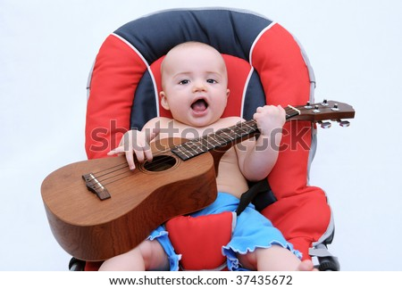 Beautiful litle baby playing guitar - stock photo