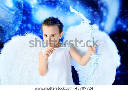 Beautiful little angel at a snowy background.