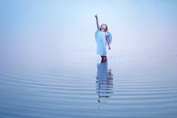Beautiful little angel girl pointing a finger at the sky and standing knee-deep in water reflected in the water surface