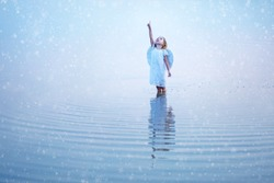 Beautiful little angel girl pointing a finger at the sky and standing knee-deep in water reflected in the water surface. Snowflakes background.