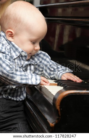 beautiful little baby boy learning plays piano