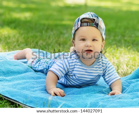 Beautiful little baby boy lying on the mat on the grass in the park