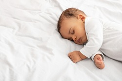 Beautiful Little Baby Boy Sleeping Peacefully Lying On Side In Bed Indoors, Resting During Daytime Sleep With Eyes Closed. Toddler Child Napping Indoors. High Angle, Cropped Shot With Copy Space