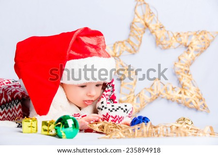 Beautiful little baby celebrates Christmas. New Year\'s holidays. Baby in a Christmas costume and in santa hat