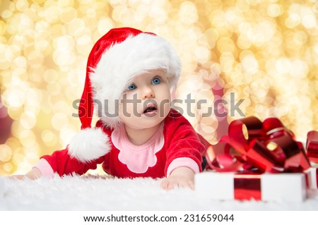 Beautiful little baby celebrates Christmas. New Year\'s holidays. Baby in a Christmas costume with gift
