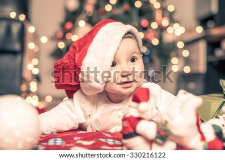 Beautiful little baby celebrates Christmas. New Year\'s holidays. Indoor winter baby portrait