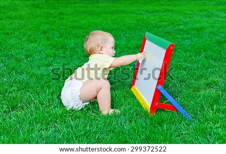 Beautiful little baby  draws sitting on a lawn