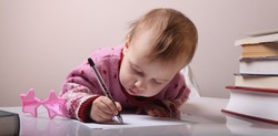 beautiful little baby girl is writing letter