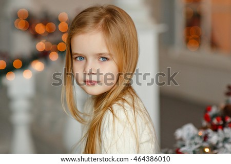 Stock Photo Beautiful little blond girl with blue eyes smiling at the New Year on the background of the Christmas tree