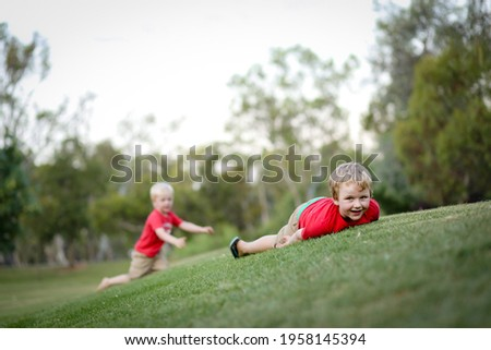 Beautiful little blonde boys rolling down grassy green hill. Outdoor nature play with children. Stockfoto ©