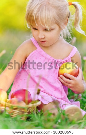 Beautiful little blonde girl sitting on grass with basket of apples, against summer green of park.