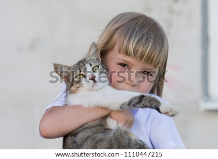 Beautiful little blonde hair girl, has fun smile face, embraces and plays with cat. Child and animals portrait. Happy amazing kids. Close up.
