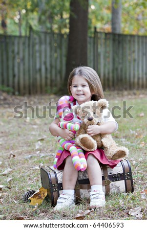 Beautiful little blue eyed brunette girl outdoors in autumn leaves with antique suitcase and Teddy bear and colorful striped sock monkey