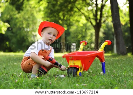 beautiful little boy in red helmet playing with a wheelbarrow in summer park