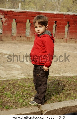 Beautiful little boy in red jacket with serious look, outdoor shot