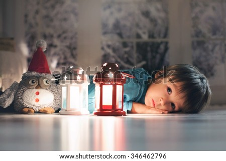Stock Photo Beautiful little boy, lying down on the floor, looking at candles, making wishes for Christmas