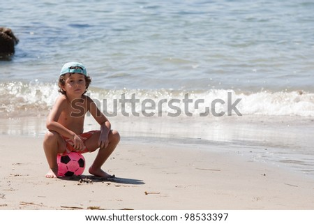 Beautiful little boy on the beach with a soccer ball