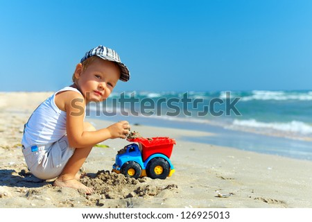beautiful little boy playing on the beach
