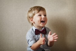 Beautiful little boy wearing a stylish maroon bow tie laughing and clapping his hands against a grey wall with vignetting