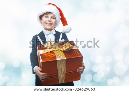 Beautiful little boy with a big Christmas gift in a Santa Claus hat. Christmas gifts for children. Smart boy Celebrates Christmas. New Year\'s holidays