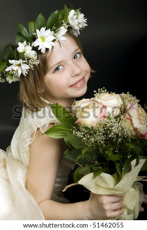 Beautiful little bridesmaid holding a bouquet of roses